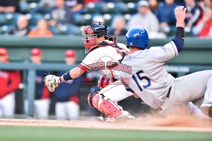Greenville Drive catcher Austin Rei (13) fields a throw home and attempts to tag out a hard sliding Brian Mundell (15) during a game against the  Asheville Tourists at Fluor Field on April 7, 2016 in Greenville South Carolina. The Drive defeated the Tourists 4-3. (Tony Farlow/Four Seam Images)