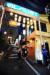 "Some 47 bars and eateries line the narrow alleyways of Nonbeiyokocho, or ""Drunkard's Alley"", in trendy Shibuya, Tokyo. Nonbeiyokocho began life immediately after World War II as group of tea houses. Though the alley is just a short walk from the central Shibuya shopping district, the rents are low due to the area being built over a river. Today 47 eateries, each with barely enough room to swing a cat, serve beer, fine wines and good, inexpensive fare."