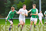 South Kerry Denis Daly breaks through the challenge of St Brendan's Andrew Byrne and Kevin Shanahan during the Minor football championship semi final in Beaufort on Thursday evening