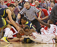 Ohio State Buckeyes forward Sam Thompson (12) and Michigan Wolverines forward Glenn Robinson III (1) hit the floor to secure a loose ball in second half action at Value City Arena on January 13, 2012.  The ball went to OSU.  (Chris Russell/The Columbus Dispatch)