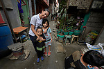 Ella Manio, a student in the Mary Johnston College of Nursing in Manila, poses with two children in the Parola neighborhood of Manila's Tondo section. Manio and other nursing students regularly visit the neighborhood to do health education and monitor the health of residents. The students also run a feeding program for neighborhood children.<br /> <br /> The nursing school is supported by United Methodist Women.