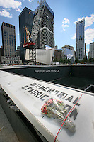 Tenth anniversary of 9/11.  Rebuilding at the World Trade Center site.  Footprint of the North Tower of the World Trade Center is part of the soon-to-be-completed 9/11 Memorial.  Names of all 9/11 victims are engraved on sides of each footprint.  Building for museum is at center, with construction of 4 WTC behind.  Photo by Ari Mintz.  8/11/2011.