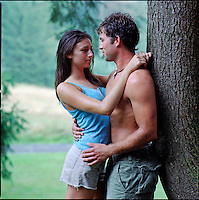 Couple embracing, leaning against a tree