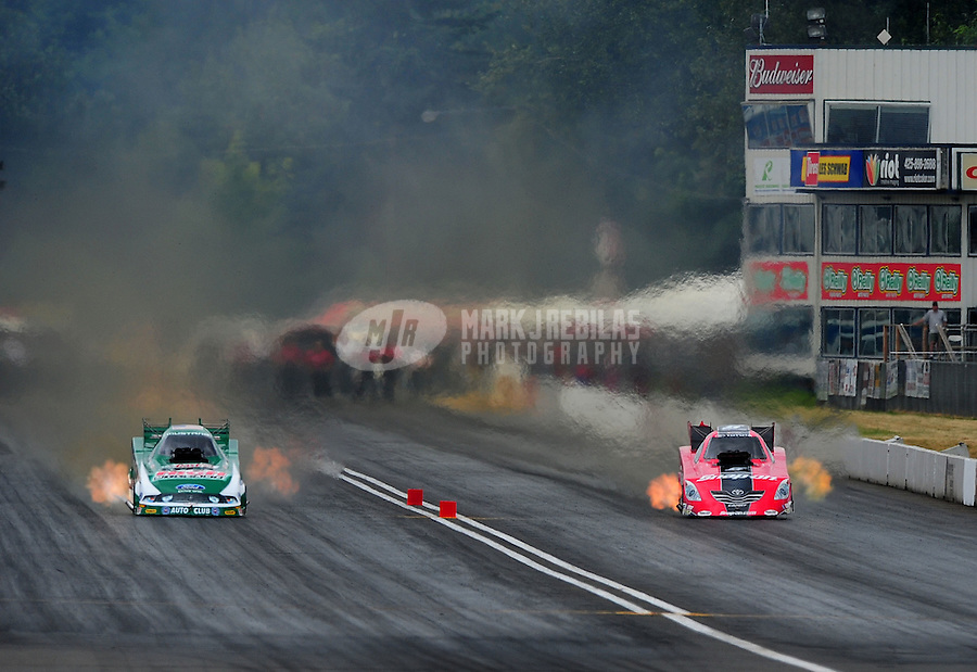 Aug. 6, 2011; Kent, WA, USA; NHRA funny car driver John Force (left) races alongside Cruz Pedregon during qualifying for the Northwest Nationals at Pacific Raceways. Mandatory Credit: Mark J. Rebilas-