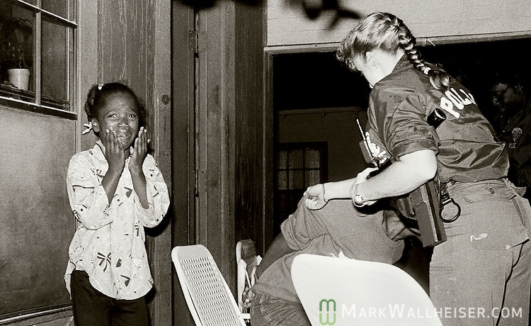 Against the backdrop of a crack raid at her home, an 8-year-old girl screams in fear and confusion while a vanload of Tallahassee Police crack-squad undercover officers emptied onto her front porch, battered down the front door and arrested her mother (R) and other family members.