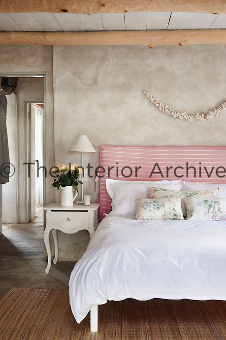 A country bedroom with a beamed ceiling and stone floor. A double bed has a striped pink fabirc headboard and floral pattern cushions.