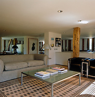 The sitting area of the open-plan living space is furnished with a glass and steel coffee table and a comfortabel sofa
