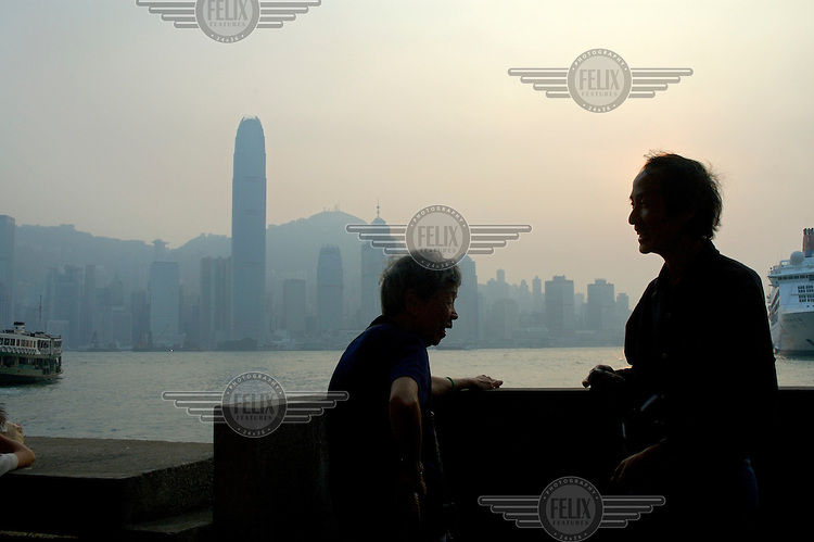 People chatting on the Kowloon waterfront at dusk, with Hong Kong island across the harbour, including Two International Finance Centre (415m), the city's tallest skyscraper, completed in 2003 on reclaimed land.