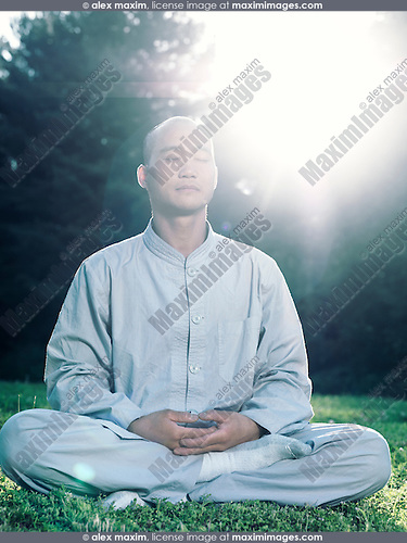 Shaolin monk meditating outdoors during sunrise in sunlight