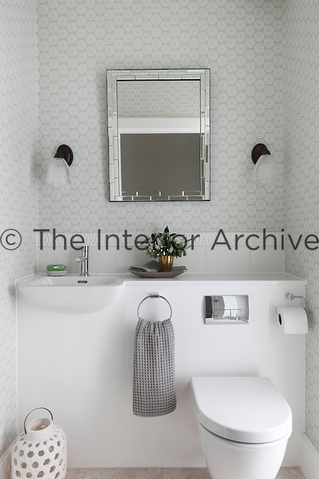 A white bathroom with pale grey and white patterned wallpaper and a boxed in sink and toilet
