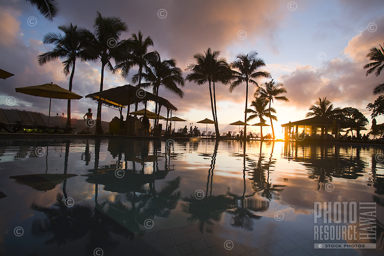 Poolside sunset at an oceanfront resort lined with palm trees