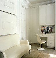 Drawings by Donald Judd hang above a sofa upholstered in white vinyl in a corner of the kitchen