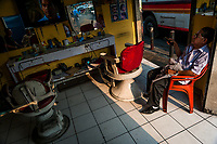 A Salvadoran hairdresser watches TV while waiting for the customers in a barber shop in San Salvador, El Salvador, 11 April 2018.
