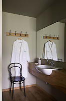 A hotel bathroom furnished simply with a Thonet chair