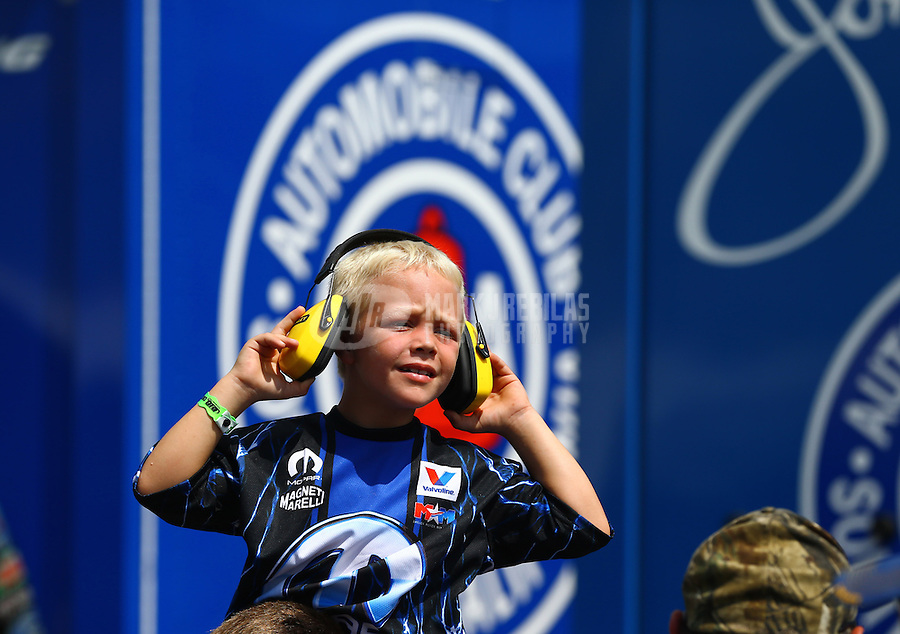 Aug. 16, 2013; Brainerd, MN, USA: A young fan of NHRA funny car driver Matt Hagan in the pits during qualifying for the Lucas Oil Nationals at Brainerd International Raceway. Mandatory Credit: Mark J. Rebilas-