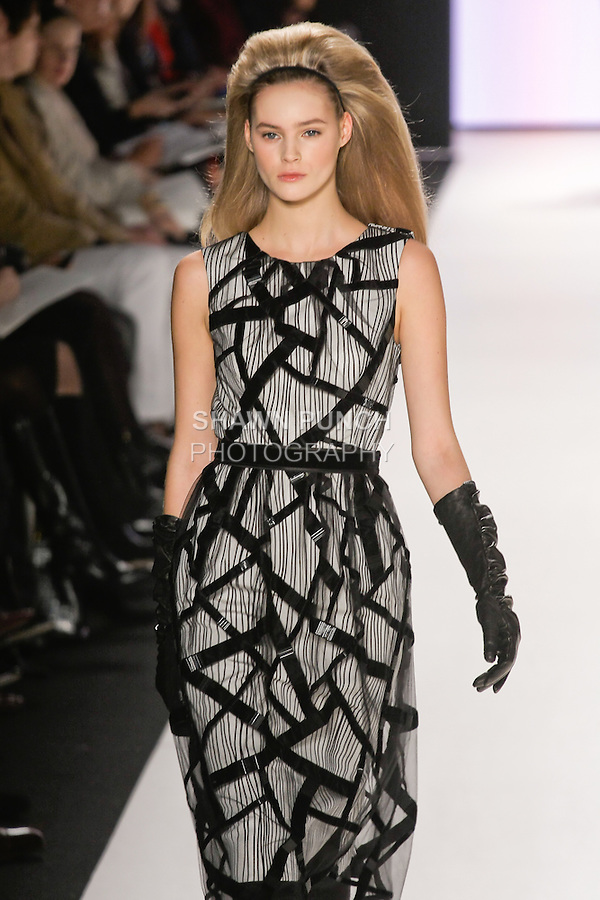 Juju Ivanyuk walks runway in a black and canvas striped print silk faille dress with embroidered tulle and ribbon overlay, black leather gloves, from the Carolina Herrera Fall 2012 collection, during Mercedes-Benz Fashion Week Fall 2012 in New York.