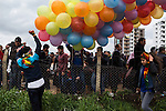 A bystander holds balloons for a balloon seller who is trying to jump over the fence to avoid standing in line at Newroz, the Kurdish New Year celebration, in Diyarbakir, Turkey, March 21, 2015. The balloon man got caught the first time and succeeded the second. Newroz, or Nowruz, is an ancient holiday celebrated by a multitude of ethnic groups across Iran, Central Asia, and the Caucuses, and ushers in the first day of Spring, March 21. For Kurds, Newroz is a means of political and cultural expression, featuring Kurdish politicians, activists, and musicians, and has become a manifestation of Kurdish identity. In Turkey, the celebrations begin a few days before the Vernal Equinox, culminating in a huge gathering in the heart of Turkey's Kurdish population, the southeastern city of Diyarbakir. This year, PKK founder Abdullah Öcalan, who despite serving a life sentence for treason still enjoys widespread influence among Kurds, sent a letter that was read at Newroz in Diyarbakir, calling for an end to the PKK's armed struggle against the Turkish state.
