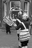 "The ""Nutters' Dance"", Bacup, Lancashire  1973.  On Easter Saturday every year the ""Coco-nut"" dancers gather at one boundary of the town and dance their way across to the other accompanied by members of the Stackstead Silver Band, collecting for charity as they go.  Here they're dancing outside an old peoples' home."