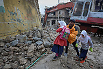 A man helps girls through the rubble as they make their way to school in the Old City of Mosul, Iraq, which was devastated during the 2017 Battle of Mosul, which led to the defeat of the Islamic State group, also known as ISIS. During control of the city by the Islamic State, most children didn't attend school.