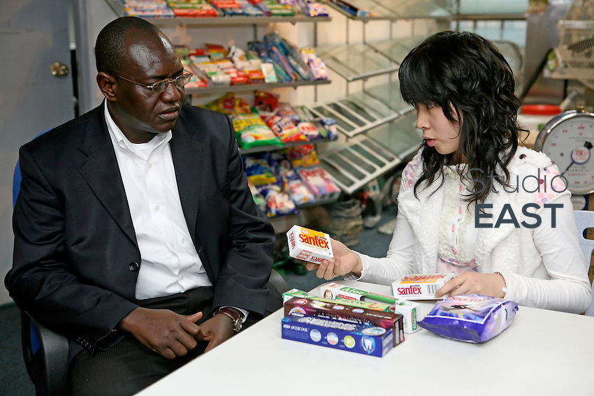 Businessman and president of the Malian community in Guangzhou Diawarra Dioncounda,left, discusses products to export with a Chinese employee, in Guangzhou, China, on March 15, 2007. Dioncounda ships up to 800 containers per year to Africa. Chinese goods flow to Africa, but men flow the other way: thousands of Africans are now settling in China. China's Southern metropolis Guangzhou has the country's largest African population, now exceeding 7,000. Photo by Patrick Wack/Pictobank