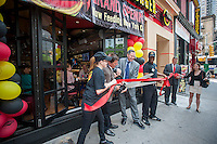 "Reise Organization Chairman and CEO Dennis Riese, center left, and Fatburger CEO Andy Wiederhorn, center right, with Fatburger employees cut the ribbon to open the new Fatburger restaurant in the Murray Hill neighborhood of  New York on its grand opening day, Tuesday, June 11, 2013. The popular West Coast chain, which has a cultish following, opened its first New York outpost  bringing their grilled to order menu with their signature collection of toppings to the East Coast. The fast casual restaurant is popular with celebrities and a loyal fan base and started in Hollywood in 1952.  the company uses ""The Last Great Hamburger Stand""  as their motto and the New York restaurants, a total of ten are planned, will be run by the franchisee, the Riese Organization. (© Richard B. Levine)"