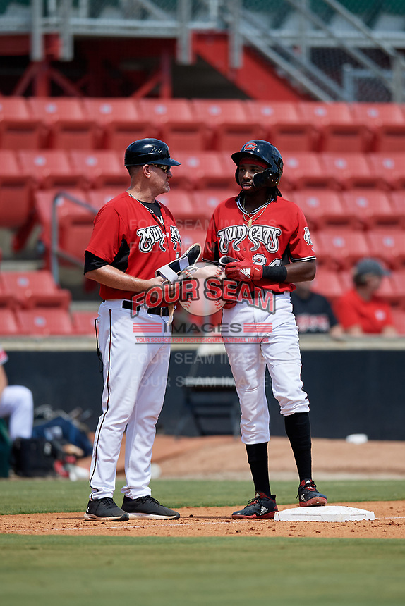 Carolina Mudcats manager Joe Ayrault (33) talks with Wes Rogers (24) during a Carolina League game against the Winston-Salem Dash on August 14, 2019 at Five County Stadium in Zebulon, North Carolina.  Winston-Salem defeated Carolina 4-2.  (Mike Janes/Four Seam Images)