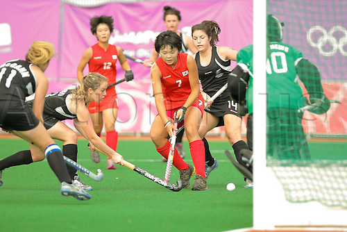 24.08.2010, Singapore Youth Olympic Games 2010 Hockey, Sengkang Hockey Stadium : South Korea's Baek Eeseul(red #7) battles for the ball just in front of New Zealand's goalposts during the Women's Bronze Medal Match between New Zealand and South Korea..
