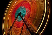 The arc of a ferris wheel in motion is bright against the night Austin, Texas sky