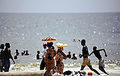 Libreville, Gabon. People on the beach and in the sea, sunny weekend; women carrying snacks for sale on trays on their heads.