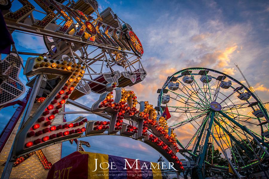 Amusement rides at a county fair at sunset.