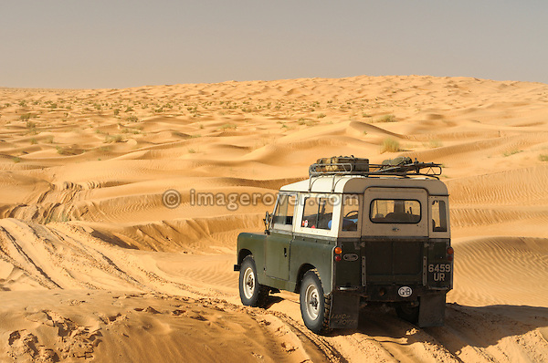 Africa, Tunisia, nr. Tembaine. A historic Land Rover Series 2a traversing through a sandfield with dunes close to Tembaine on the eastern edge of the Grand Erg Oriental. --- No releases available, but releases may not be needed for certain uses. Automotive trademarks are the property of the trademark holder, authorization may be needed for some uses.  --- Info: Image belongs to a series of photographs taken on a journey to southern Tunisia in North Africa in October 2010. The trip was undertaken by 10 people driving 5 historic Series Land Rover vehicles from the 1960's and 1970's. Most of the journey's time was spent in the Sahara desert, especially in the area around Douz, Tembaine, Ksar Ghilane on the eastern edge of the Grand Erg Oriental.