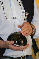 In the wine tasting room, Pascal Delbec, owner and wine maker holding a decanter carafe of wine Chateau Belair (Bel Air) 1er premier Grand Cru Classe Saint Emilion Bordeaux Gironde Aquitaine France