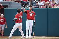 Scott Holzwasser (28) of the Northeastern Huskies is greeted at home plate by teammate Max Burt (24) after hitting a home run against the North Carolina State Wolfpack at Doak Field at Dail Park on June 2, 2018 in Raleigh, North Carolina. The Wolfpack defeated the Huskies 9-2. (Brian Westerholt/Four Seam Images)