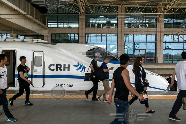 Passengers disembark from a high-speed train.