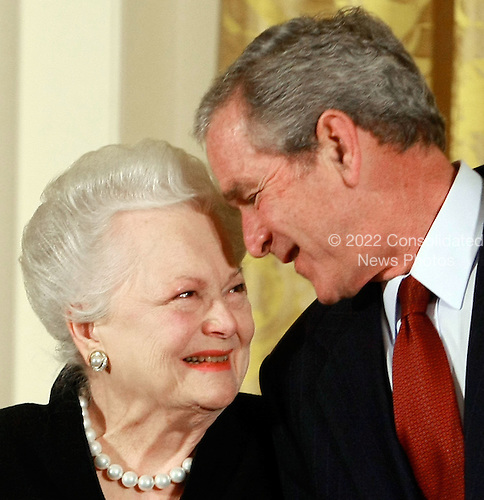 Washington, DC - November 17, 2008 -- United States President George W. Bush congratulates actress Olivia de Havilland before presenting her with the 2008 National Medals of Arts award during an event in the East Room at the White House on Monday, November 17, 2008 in Washington, DC. During the event president Bush presented recipients with awards for the National Medals of Arts and the National Humanities Medal.  .Credit: Mark Wilson - Pool via CNP