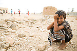 Boy near soccer game played on rock field between buildings, Hawf Protected Area, Yemen