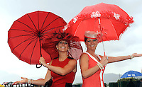 KILLARNEY RACES THURSDAY 16-7-09: Sisters Olivia and Una Buckley from Listowel shelter from the rain at the Dawn Dairies Queen of Fashion at Killarney races on Thursday.<br /> Picture by Don MacMonagle