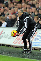 Swansea head coach Francesco Guidolin picks up the ball during the Barclays Premier League match between Swansea City and Crystal Palace at the Liberty Stadium, Swansea on February 06 2016