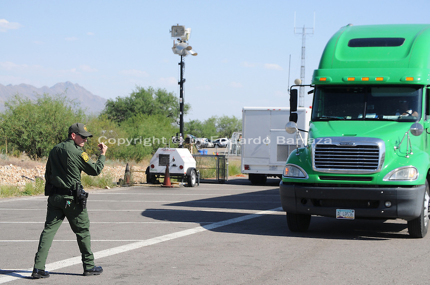 Nogales, Arizona - A Border Patrol agent assigned at a permanent U.S. Customs and Border Protection (CBP) traffic checkpoint located on highway Interstate 19, north from Nogales and near the Town of Tubac, Arizona gives directions to the driver of a semi-truck he is subjecting to secondary inspection. Border Patrol checkpoints serve as inspection stations to detect illegal immigration and drug smuggling. Border Patrol agents assigned to fixed traffic checkpoints have wide discretion to stop vehicles for brief questioning and inspection of its occupants and its contents. This checkpoint is part of the Border Patrol Tucson Sector. Photo by Eduardo © 2012
