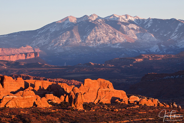 Sunset light over the Entrada Sandstone fins of the Fiery Furnace in Arches National Park near Moab, Utah, USA, with the snow-capped La Sal Mountains in the background.