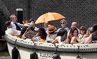 Nederland - Amsterdam - 2010. Zomer in Amsterdam. Rondvaart in een sloep. Toeristen zitten met een paraplu in de zon. Foto Berlinda van Dam / Hollandse Hoogte.
