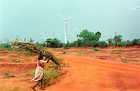 INDIA Muppandal, wind farm with wind turbines and woman carry firewoods on her head at Cape Comorin / INDIEN Frau traegt Feuerholz, Hintergrund Windpark