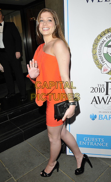 NIKKI SANDERSON .At the Professional Footballers' Association Awards, Grosvenor House hotel, Park Lane, London, England, UK, 25th April 2010..PFA full length red orange one shoulder dress black clutch bag peep toe shoes smiling side hand waving .CAP/CAN.©Can Nguyen/Capital Pictures.
