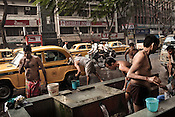 Street dwellers wash themselves while others wash cars on the streets of Kolkata in West Bengal, India.