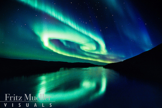 Swirling aurora borealis reflected in the Stewart River, Yukon