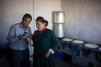 "Mongolian herder Renqima and husband Tegan Bayar use mobile phones to communicate with clients buying Urum, a traditional Mongolian ""White butter"" or clotted cream, from their dairy farm in Damao Banner, Inner Mongolia, China,2014."
