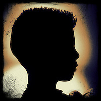 Young boy with spiked haircut silhouetted against wall lit by lap with shade.