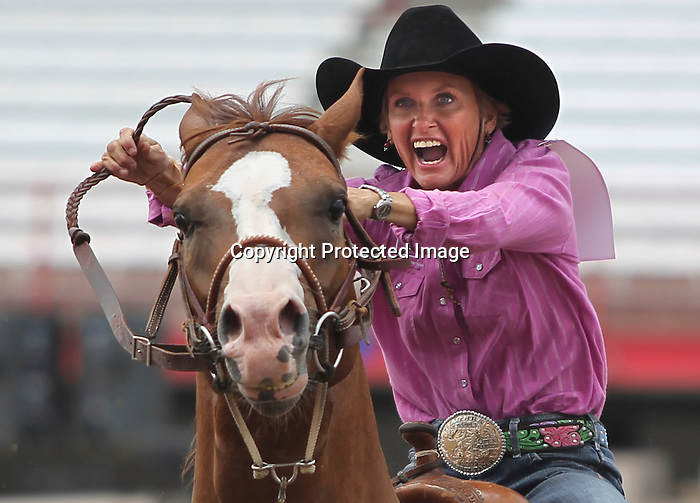 Lisa Anderson of Moore, Texas yells as she heads to the second barrel during the opening round barrel racing at Frontier Park Tuesday afternoon. Anderson recorded a time of 18.42 seconds during the competition. Michael Smith/staff