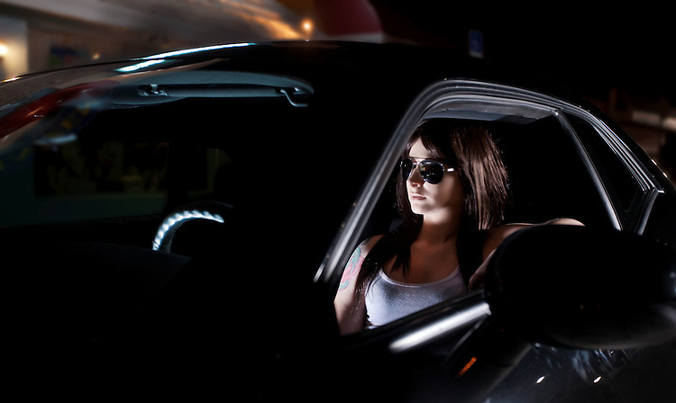 Young Woman Sitting in Black Car at Night