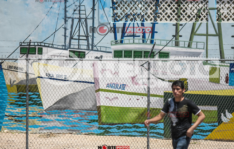 Un joven camina a un costado de un mural o pintura de baros pesqueros en una tienda de pescado y marisco en el bulevar